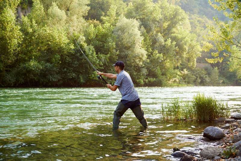 fisherman-standing-near-river-and-holding-fishing