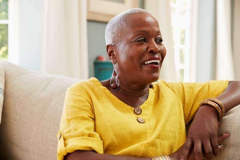 smiling-senior-woman-sitting-on-sofa-at-home