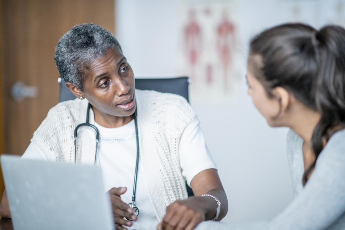 Doctor explaining link between hepatitis C and cirrhosis to patient.