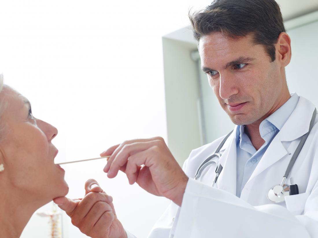 doctor looking in female patients throat
