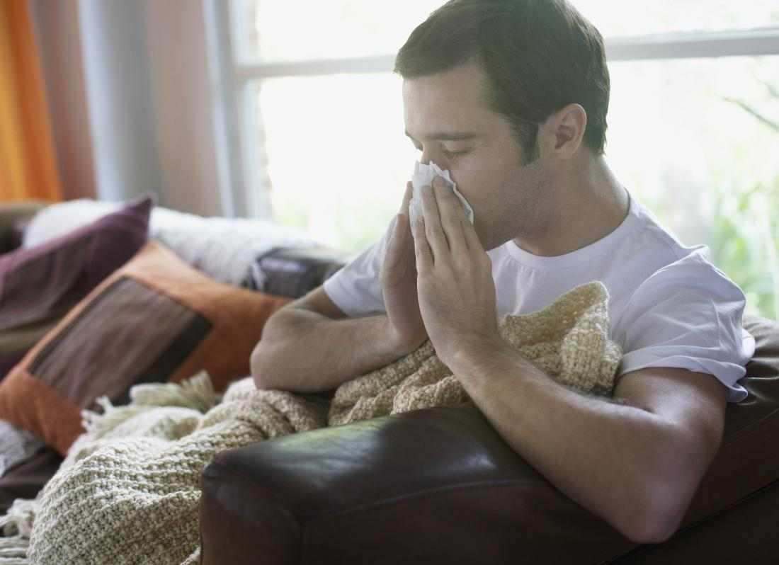 man sitting on a sofa blowing his nose