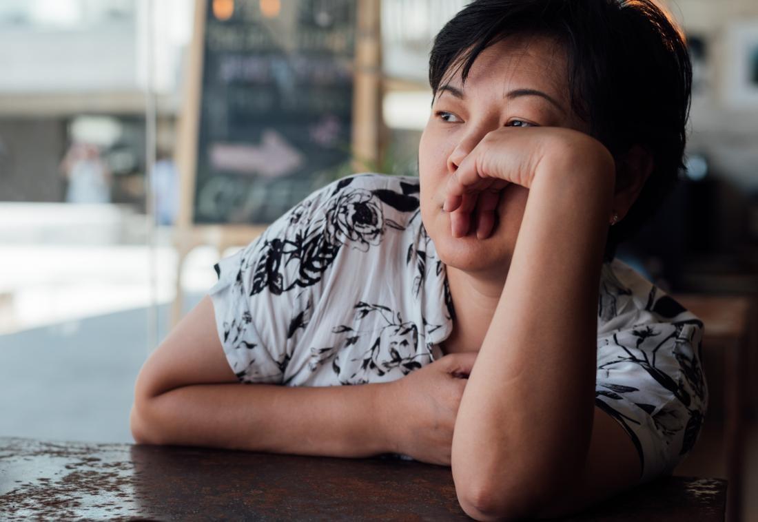 Tired mature woman leaning on table looking bored and depressed