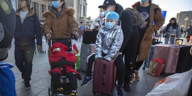 Travelers wear face masks as they walk outside of the Beijing Railway Station in Beijing.