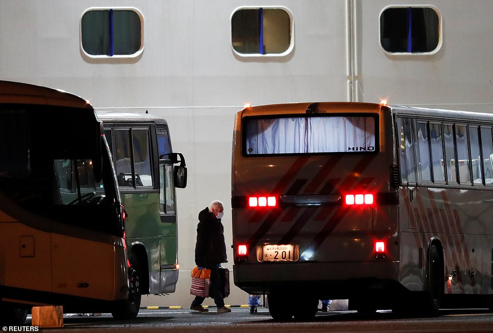 A British passenger gets on a bus after leaving the coronavirus-hit cruise ship Diamond Princess, which is docked at the Daikoku Pier Cruise Terminal in Yokohama